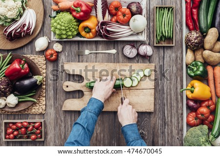 Man cooking and slicing fresh vegetables on a rustic kitchen worktop, healthy eating concept, flat lay #474670045