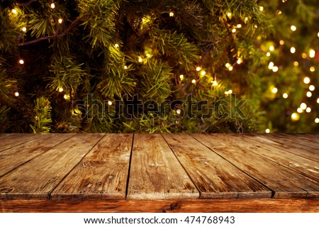 Christmas and New year background with empty dark wooden deck table over christmas tree and blurred light bokeh. Empty display for product montage. Rustic vintage Xmas background. Royalty-Free Stock Photo #474768943