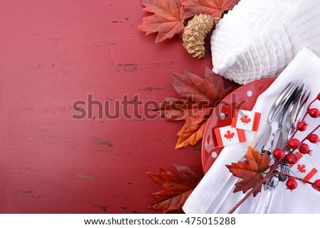 Canada red and white theme Thanksgiving background with decorated borders on a distressed red wood table, with a white turkey tureen and Canadian Maple Leaf Flag.