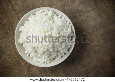 Bowl of organic rice on wooden table #475062472