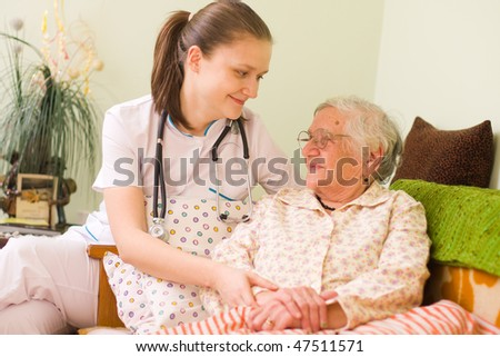 A young doctor / nurse visiting an elderly sick woman holding her hands with caring attitude. #47511571