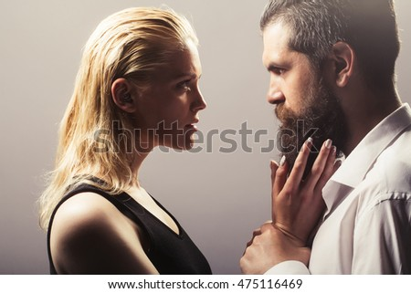 young sexy couple of pretty woman with blonde hair and handsome bearded man with long beard embracing on grey background #475116469