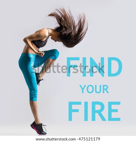 """Beautiful young fit modern dancer lady in blue sportswear warming up, working out, dancing with her long hair flying, full length, studio image on gray background. Motivational phrase """"Find your fire"""""""