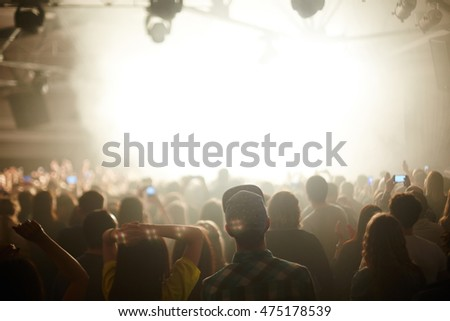 Rear view image of large crowd in front stage in bright light, watching music performance and dancing, focus on young couple in foreground #475178539
