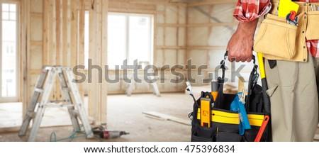 Hand of handyman with a tool bag. #475396834