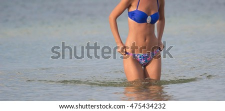 Beautiful girl on sunny tropical beach in bikini. Clouse up #475434232