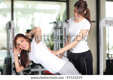 Two happy young women in the gym smiling to the camera #47553259