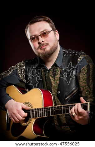 man with a guitar on a dark red background #47556025