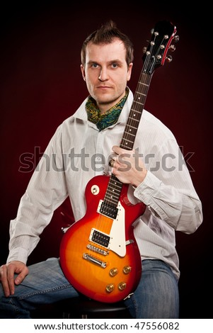 man with a guitar on a dark red background #47556082