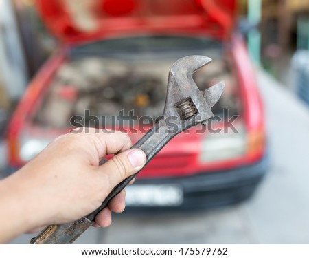 Wrench in hand on the background of cars #475579762