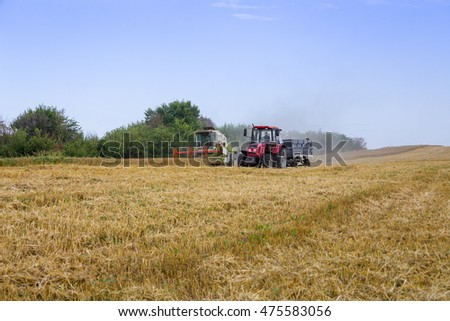 Burgas - July 4: Harvest - harvester and tractor trailer harvest of wheat field July 4, 2016, Burgas, Bulgaria #475583056