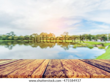 Wood pier or an old wooden table with blur image of lake and blue sky in background
