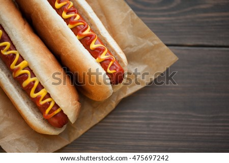 Barbecue Grilled Hot Dog with Yellow Mustard and ketchup on wooden table  #475697242