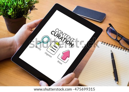 hands of a man holding a tablet with content curation concept over a wooden workspace table. All screen graphics are made up.