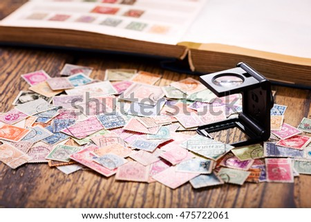 Old postage stamps from various countries on wooden table #475722061