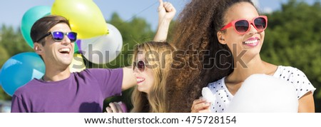 Young man with baloons standing behind two women with the candyfloss