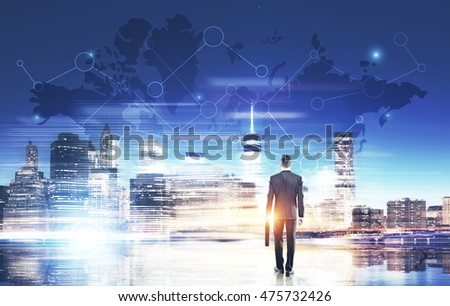 Man in suit holding suitcase standing near big city panorama with world map in the sky. Concept of multinational corporation. Toned image. Double exposure. Elements of this image furnished by NASA #475732426