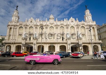 HAVANA, CUBA - JUNE 10, 2016: A restored classic convertible operating as a taxi drives along Paseo de Marti past the Great Theater (Gran Teatro de La Habana).  #475934914