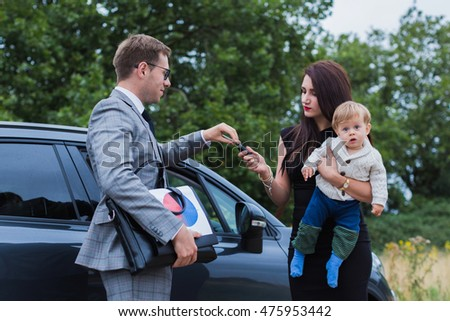 young family makes car purchase. A young boy at the hands of her mother. Happy baby reaches for the keys #475953442