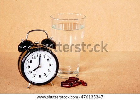 Medical  pill and water with alarm clock on wood table in the time for healthy #476135347