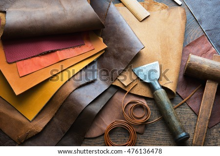 Leather craft or leather working. Selected pieces of beautifully colored or tanned leather on leather craftman's work desk . Piece of hide and working tools on a work table. Royalty-Free Stock Photo #476136478