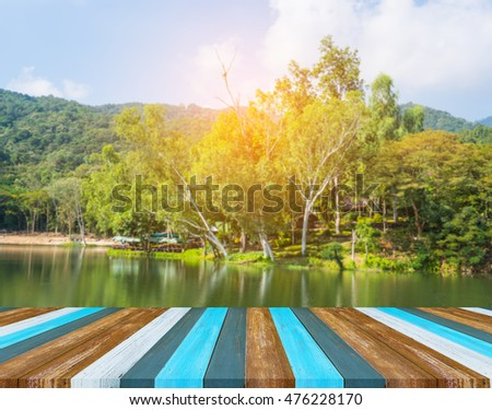 Wood pier or walkway or an old wooden table with blur image of lake and sunset sky in background. #476228170