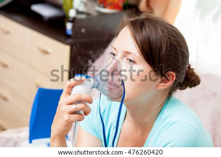 Young woman doing inhalation with a nebulizer at home #476260420