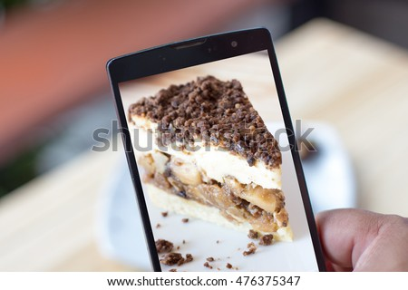 A man show nice cake Photo on his smartphone that he took before eating ,Lifestyle take photo before eating