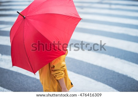 Woman with umbrella crossing the pedestrian. Selective focus on the hand. #476416309