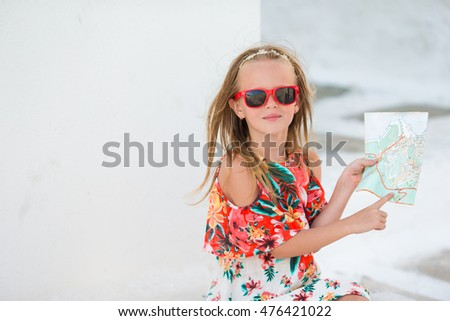 Little girl with map of island outdoors in old streets an Mykonos. Kid at street of typical greek traditional village with white walls and colorful doors on Mykonos Island, in Greece #476421022