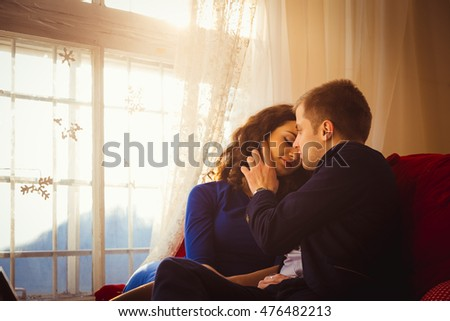 Man touches woman;s cheek tender while sitting on the pillows before window #476482213