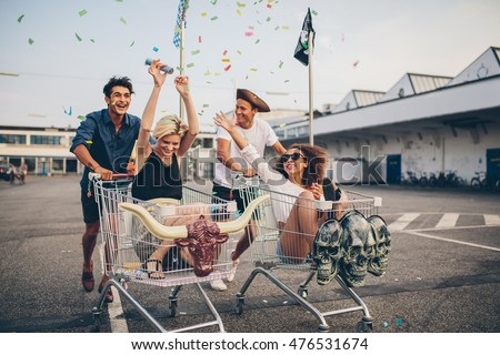 Young friends having fun on shopping trolleys. Multiethnic young people racing on shopping cart. Royalty-Free Stock Photo #476531674