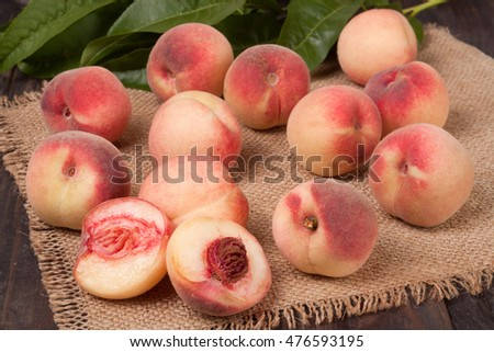 peaches in a wicker basket with leaves on wooden table #476593195