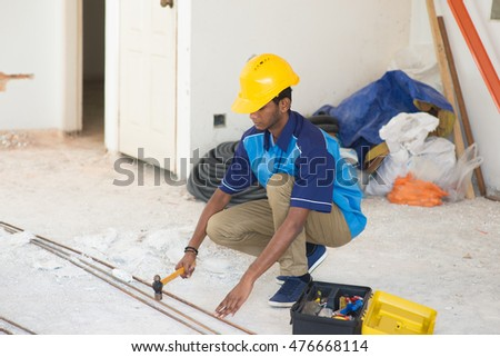 indian male contractor on site using hammer #476668114