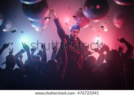 DJ or singer has hand up at disco party in club with crowd of people. #476725045
