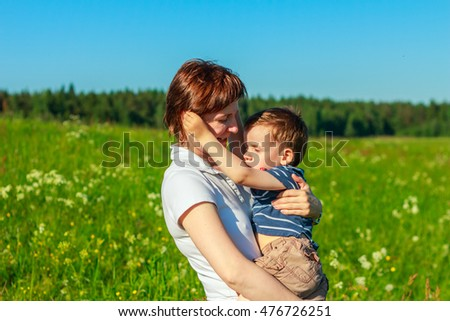 Young brunette with short hair playing with his son in the field. Family fun outdoors. #476726251