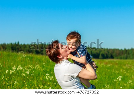 Young brunette with short hair playing with his son in the field. Family fun outdoors. #476727052