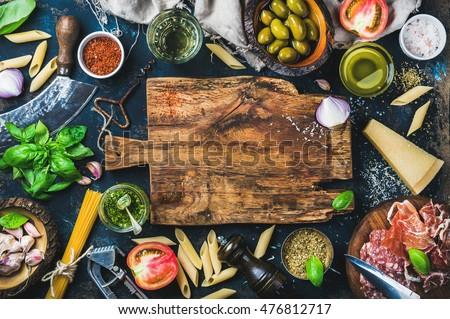 Italian food cooking ingredients on dark background with rustic wooden chopping board in center, top view, copy space Royalty-Free Stock Photo #476812717