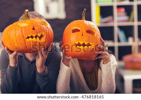 Man and woman having fun with Halloween pumpkin #476818165