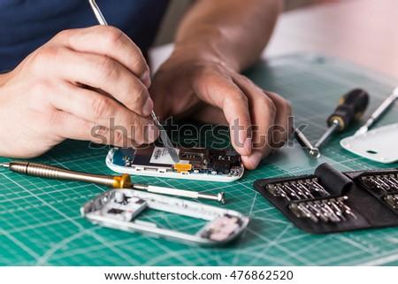 Man repairing broken smartphone, close up photo #476862520