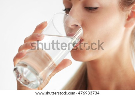 Beautiful girl drinking water on light background #476933734