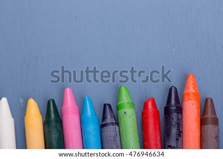 Wax crayons on a blue wooden background #476946634