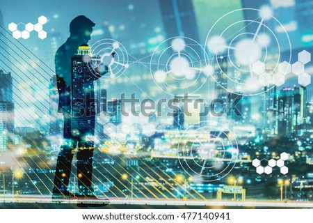 Digital revolution and Internet of Things concept. Double exposure of night city light and silhouette of business man standing and using smart phone with futuristic connection icons. #477140941