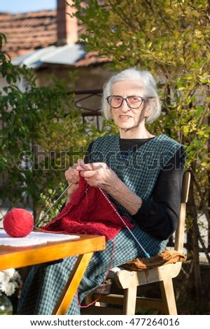 Senior woman knitting with red wool outdoors #477264016