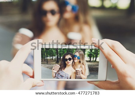 Two girls friends with coffee take away outdoors and someone POV view, taking photos at digital camera of smartphone. Young females at mobile screen, having fun in summer park. Lifestyle portrait. #477271783