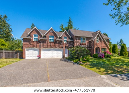 Big custom made luxury house with nicely trimmed and landscaped front yard in the suburbs of Vancouver, Canada. #477551998