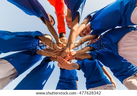 kids soccer team in huddle Royalty-Free Stock Photo #477628342