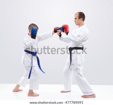 Boy karateka is  training strikes on the trainer overlays #477789091