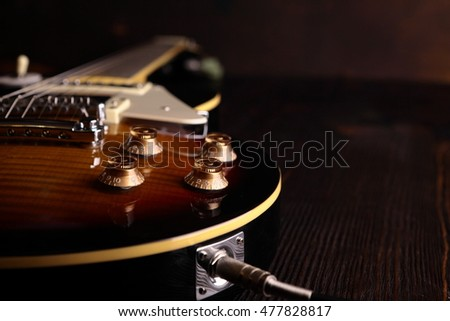 Old electric guitar on wooden table and background #477828817