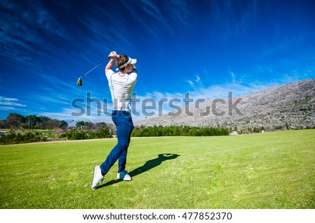 Close up image of a male golfer playing a shot on the fairway on a golf course in south africa #477852370